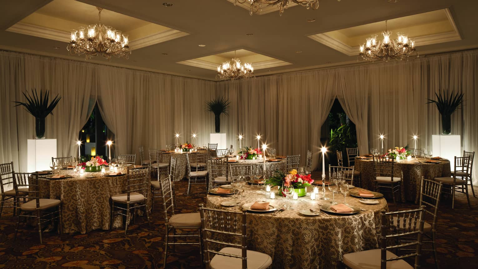 Round candle-lit banquet dining tables in ballroom