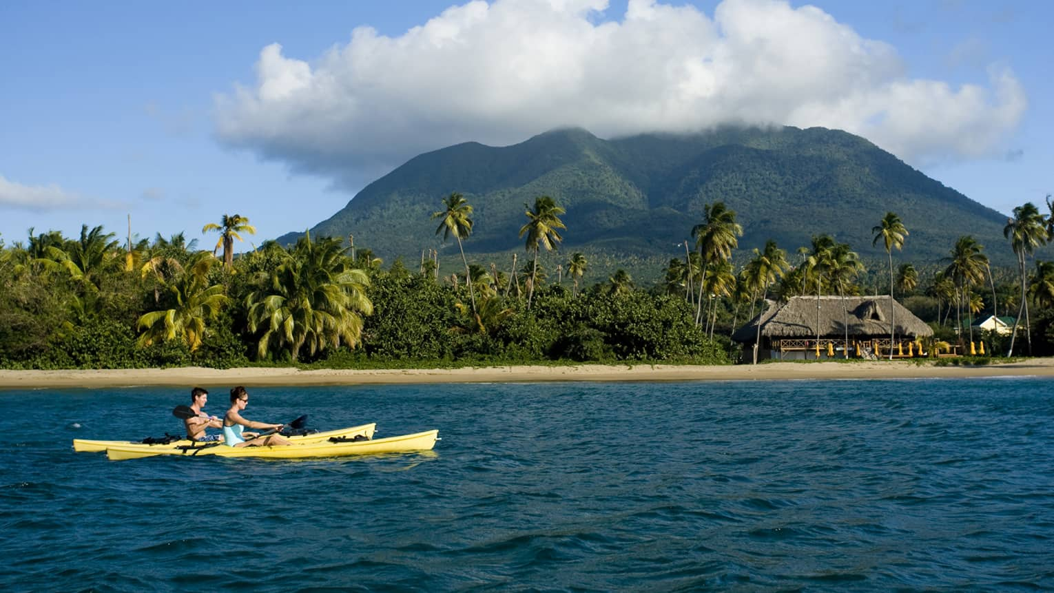 Two people in yellow kayaks on ocean by sand beach, small villa with thatched roof