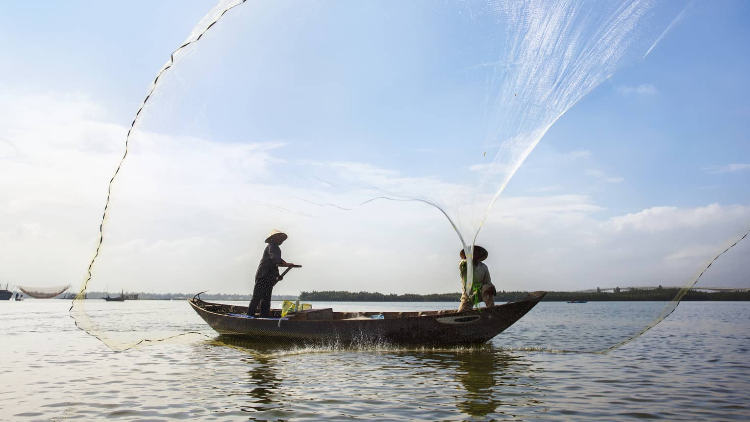 Silhouettes of two people wearing hats in small boat standing, casting large nets