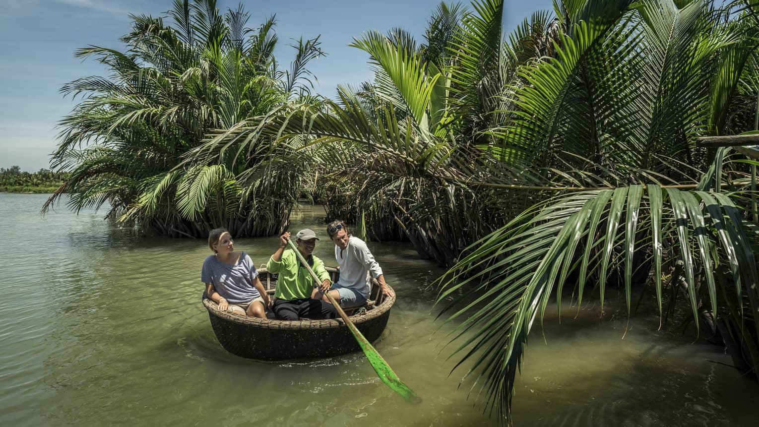 A couple and a guide in a Hoi An tour basket boat