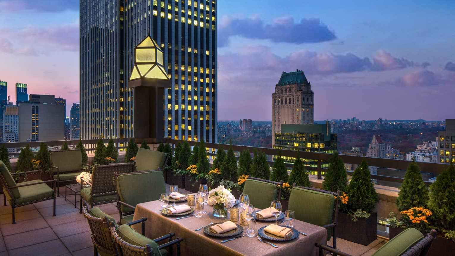 Private patio dining table with plush green cushions on chairs on rooftop terrace, city views at dusk