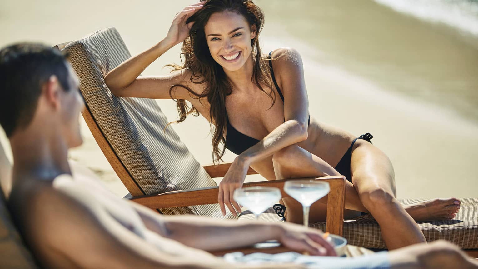 Smiling woman wearing black bikini sits on side of beach chair, faces man