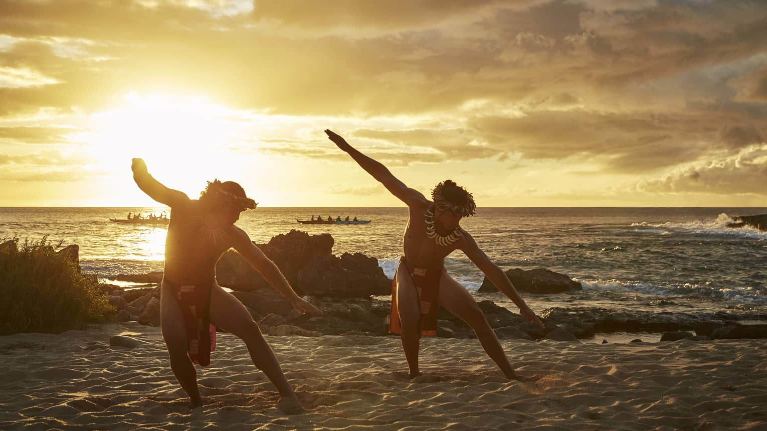 Two Hawaiian dancers with arms outstretched pose on sandy beach at sunset