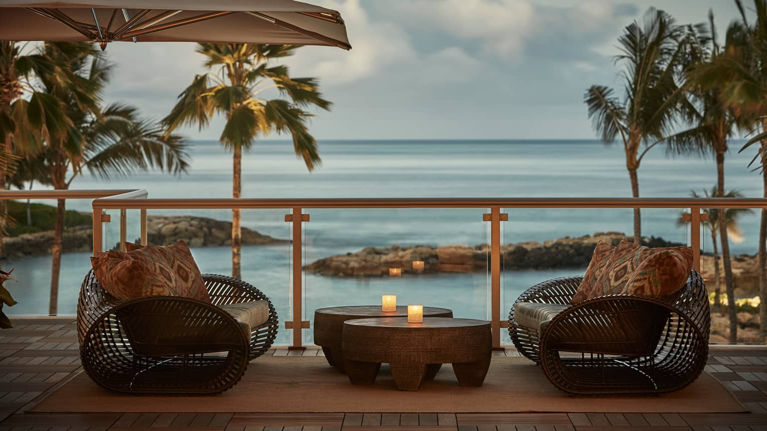 Large rattan chairs with print pillows, table with candles on Hokulea patio at sunset