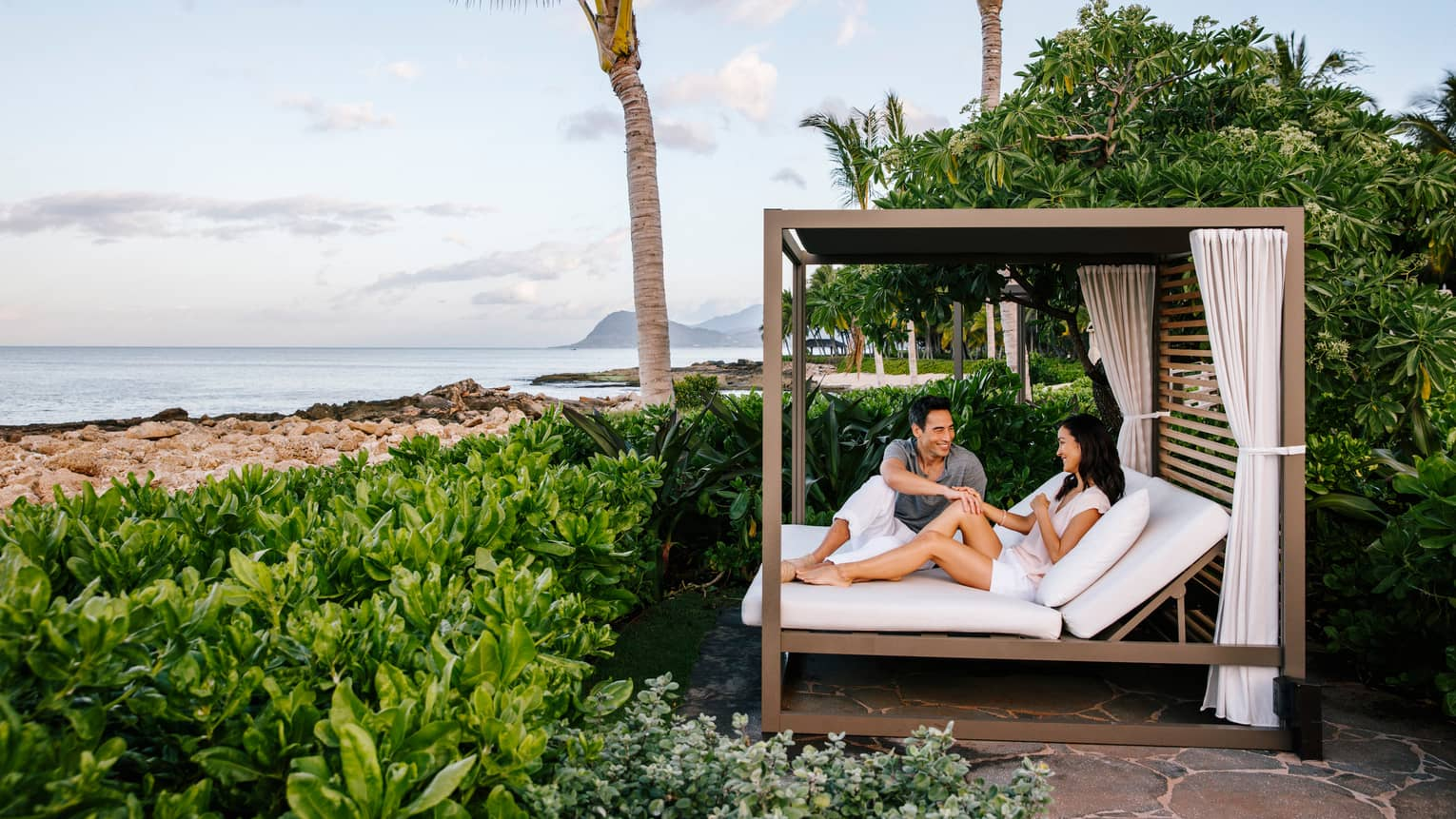 Man and woman relax on patio bed under wood cabana by large hedge, beach
