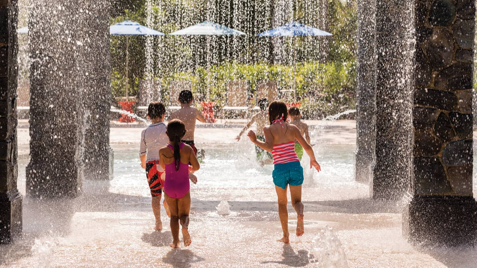 Children run past pillars, splash under falling water on Splash Zone water park