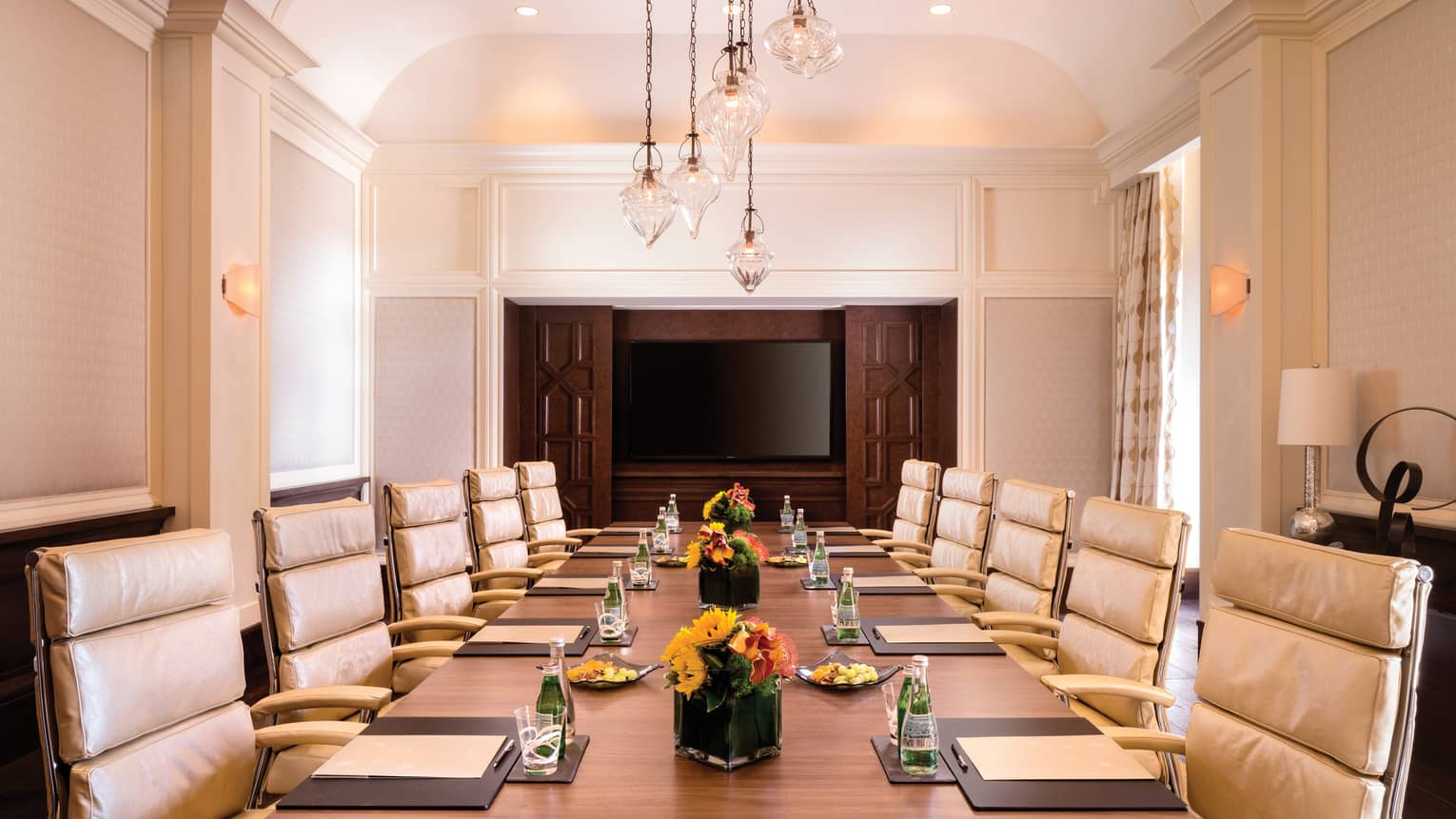 Executive Boardroom with large meeting table set with agendas and flowers, lined with tan leather chairs