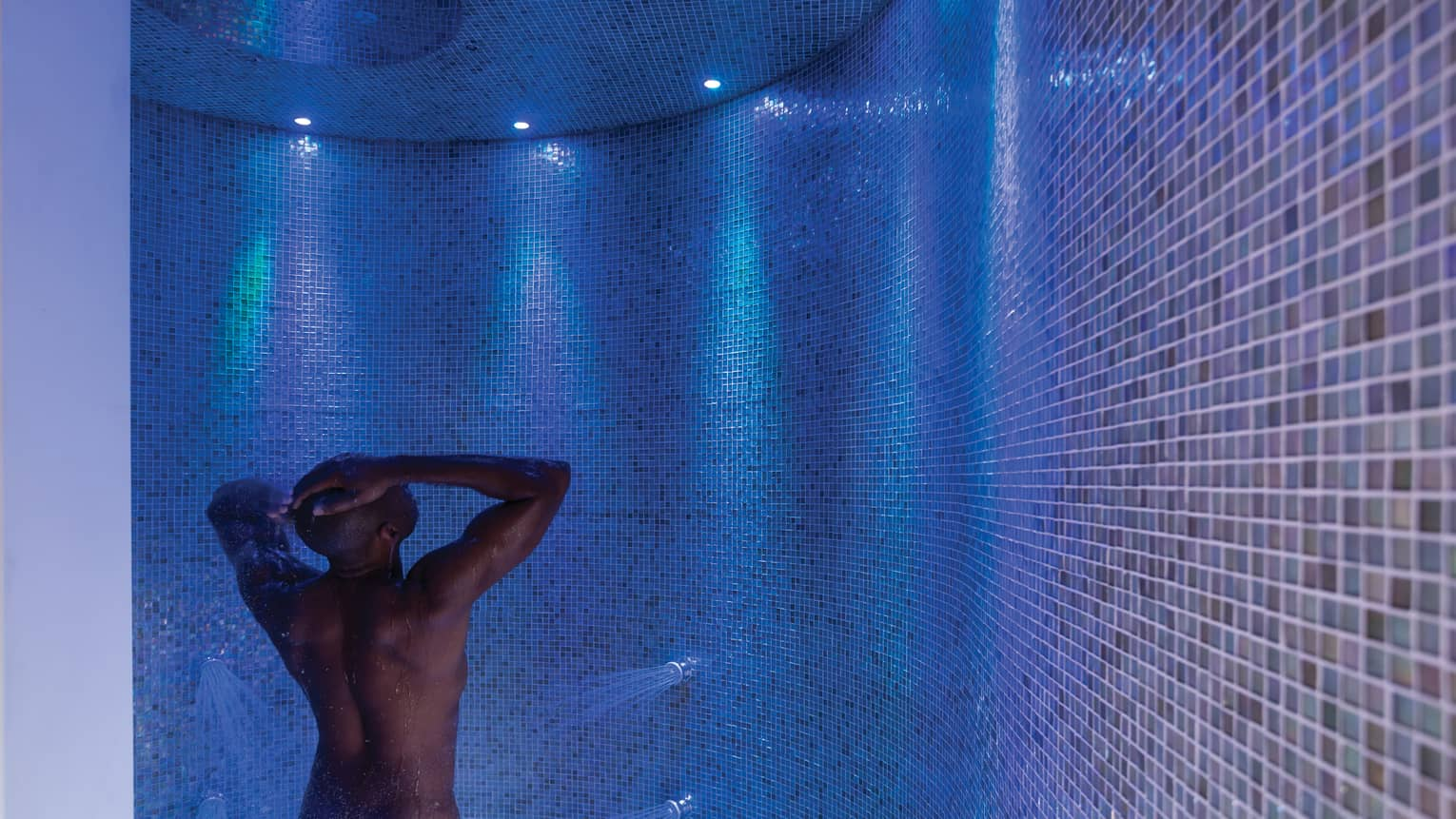 Man rinses off in tile spa shower under blue, purple lights