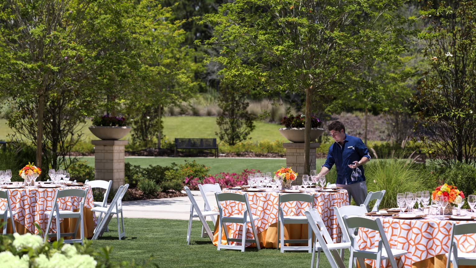 A four seasons server sets tables outside on the lady palm lawn at four seasons resort orlando at walt disney world