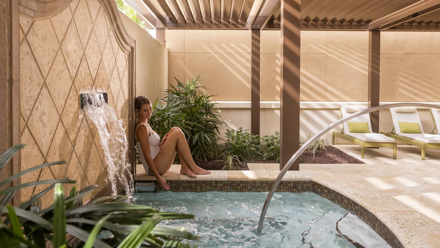 Woman wearing swimsuit leans against tile wall with fountain by small spa pool