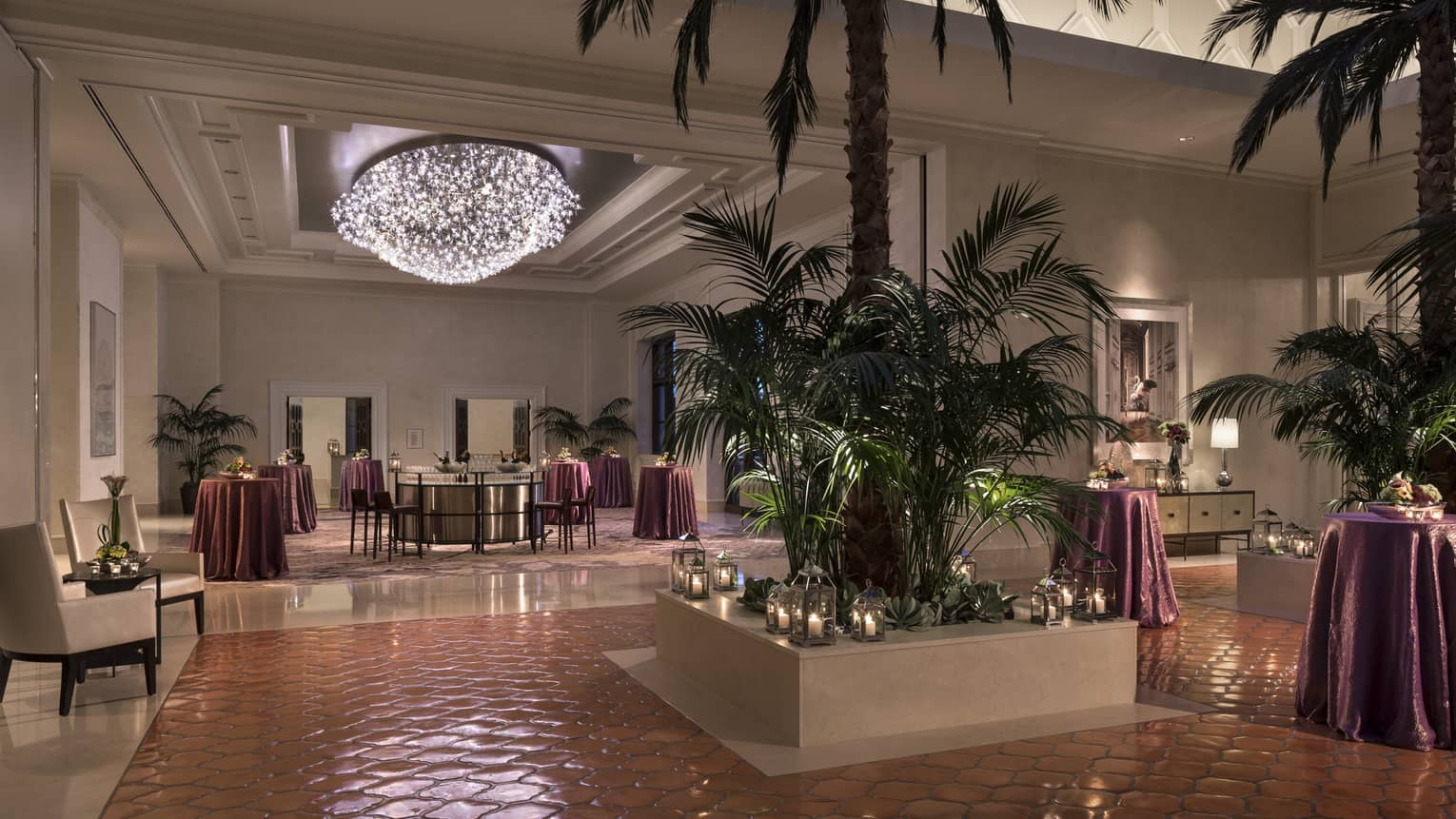 Grand Ballroom Foyer with potted palm trees and candles, cocktail lounge tables under light