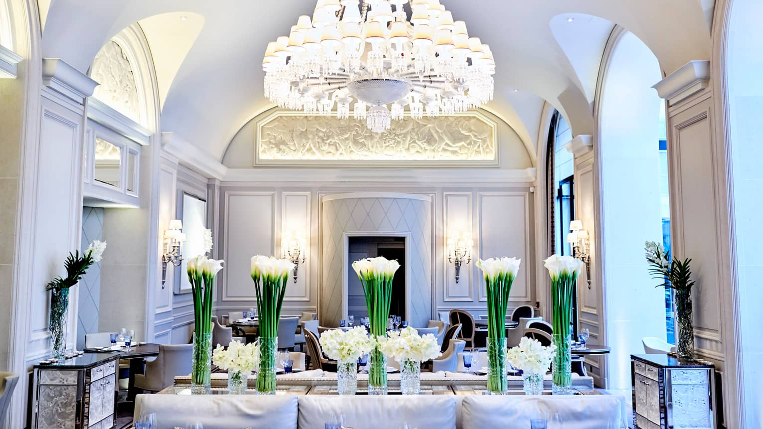 Le George dining room, white flowers in vases under large crystal chandelier