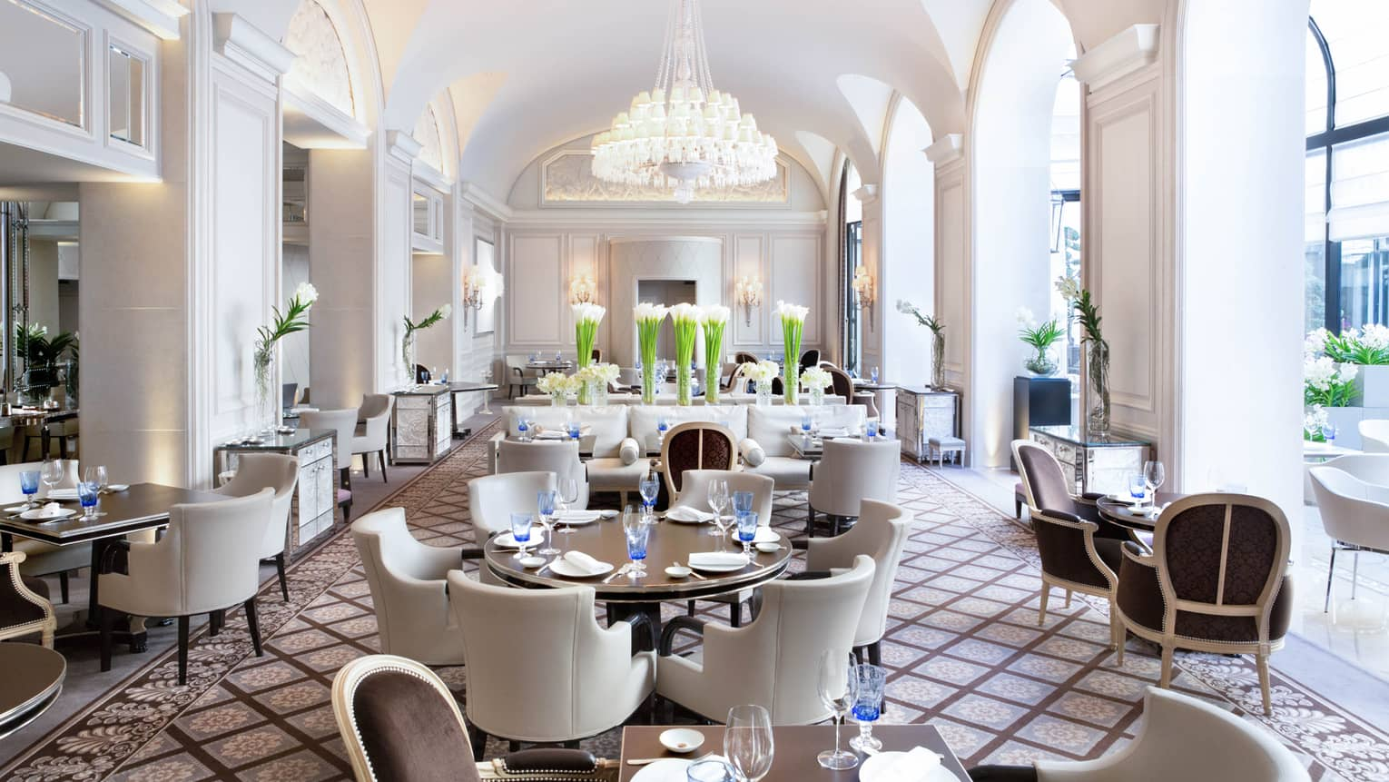 Bright Le George dining room, white chairs around tables under arched pillows, chandeliers