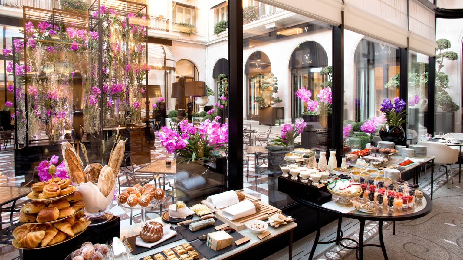 Pastries, desserts spread over tables in Parisian bakery, purple flower arrangements