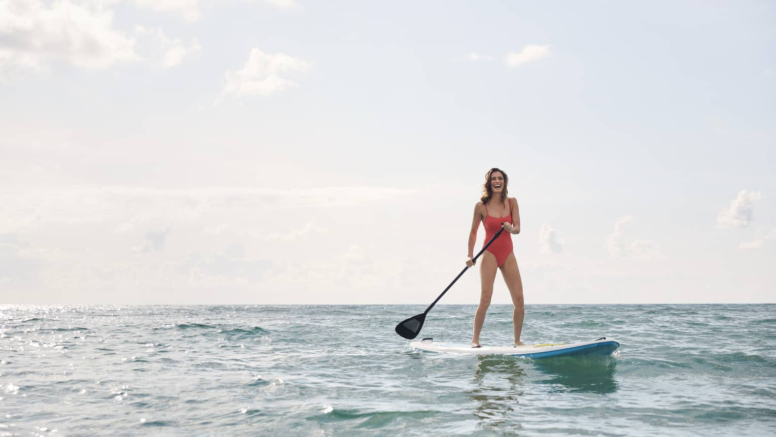 Woman wearing pink bathing suit paddle-boards across clear waters