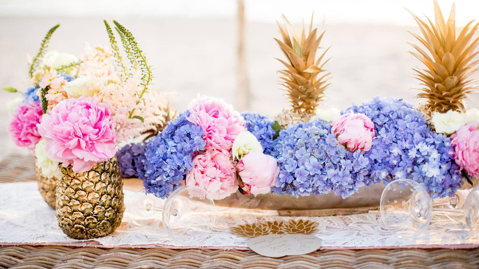 Vibrant pink and purple flowers are displayed around pineapples