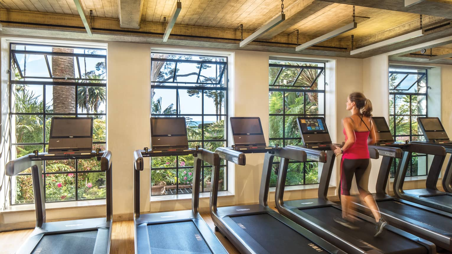 Woman runs on row treadmill in row of machines by large open windows in Fitness Centre