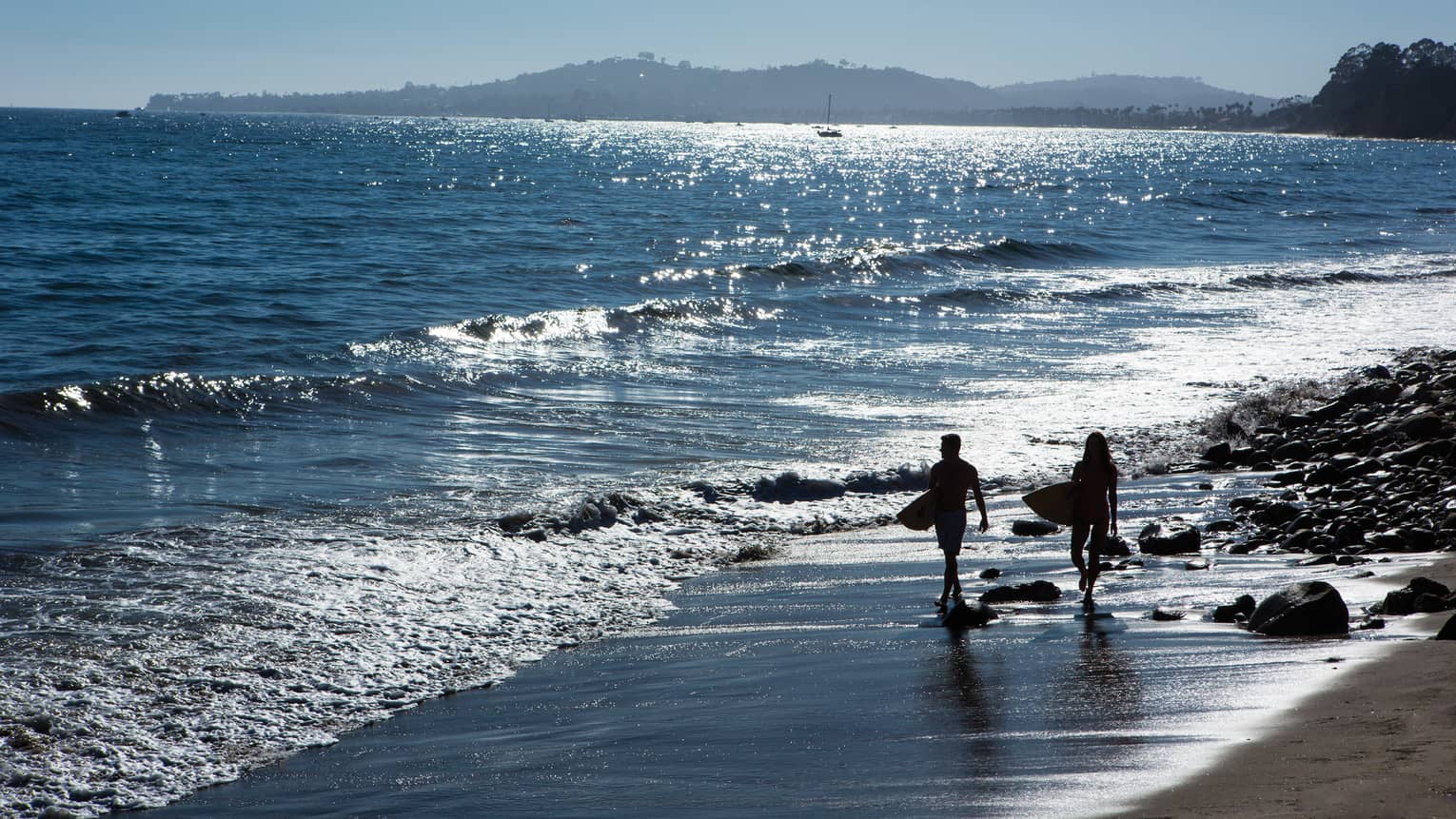 Silhouettes of two people carrying surfboards along beach shoreline