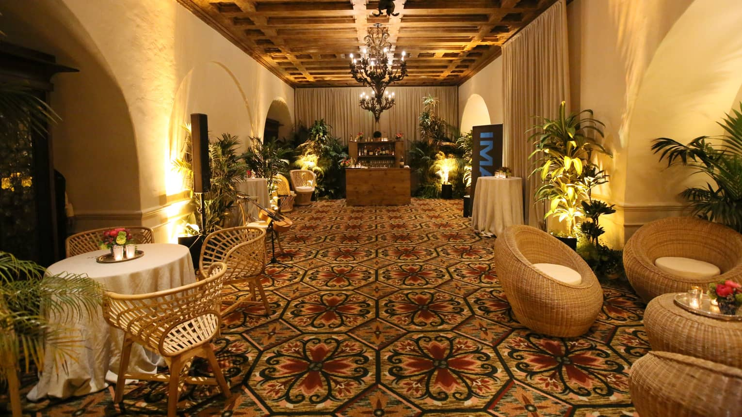 La Salita carpeted event room with wicker lounge furniture, small wood bar