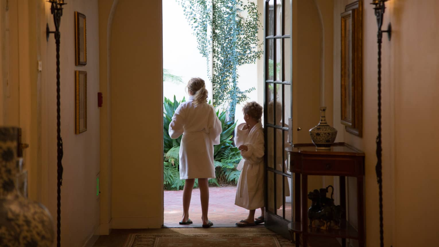 Two children wearing white bathrobes stand in hotel bungalow doorway, look outside