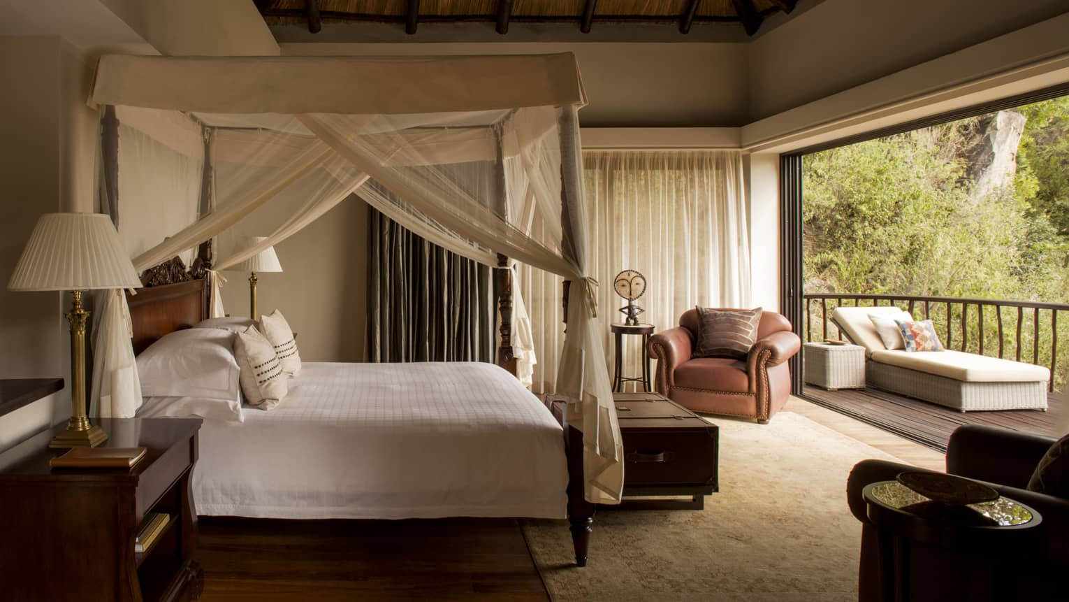 Two-bedroom villa side of poster bed with white canopy, open patio wall