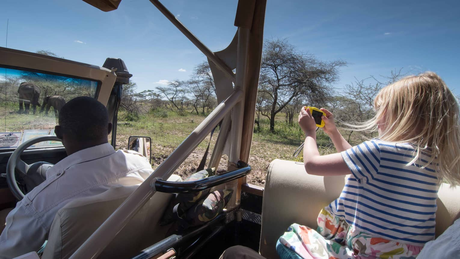 Young girl takes photos of elephants from backseat of safari Jeep