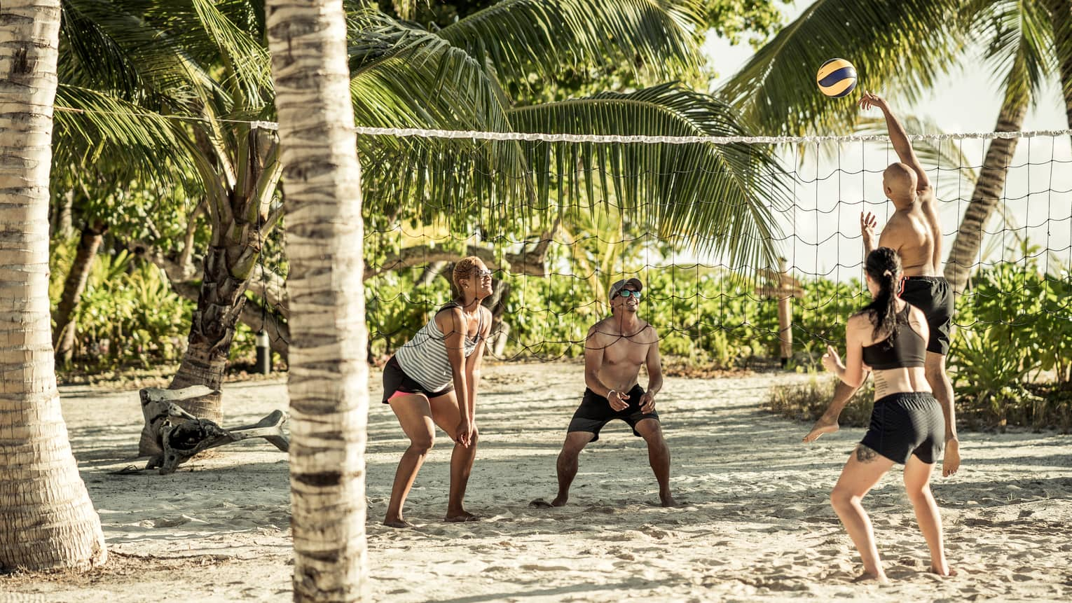 Four people playing volleyball on the beach