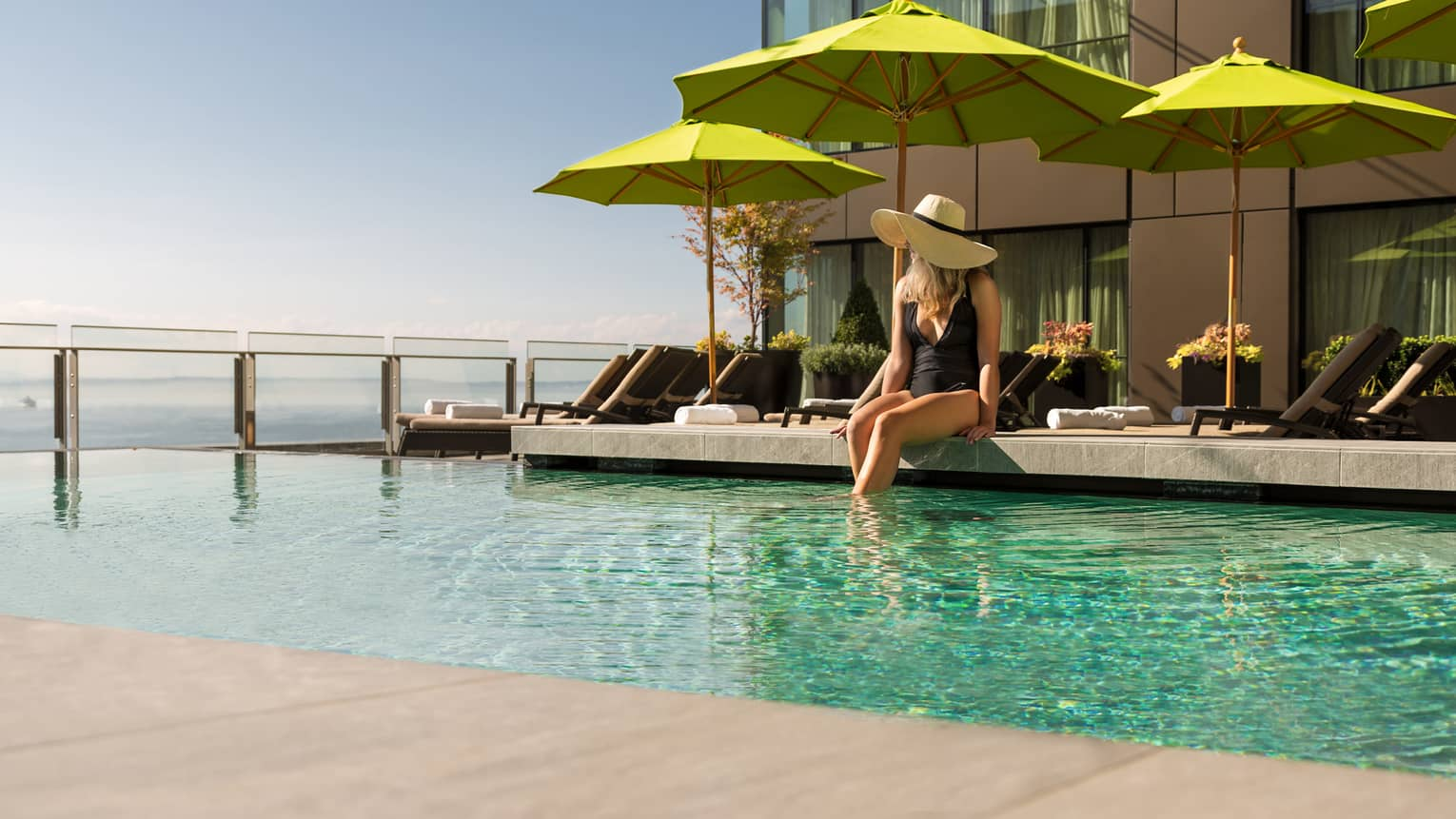 Woman in black swimsuit, sunhat sits on ledge of pool in front of green patio umbrella