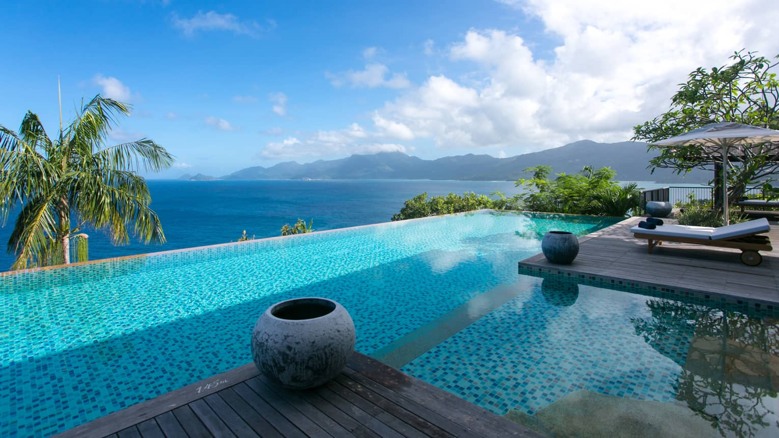Six-Bedroom Residence Villa infinity pool beside top of palm tree, ocean view below
