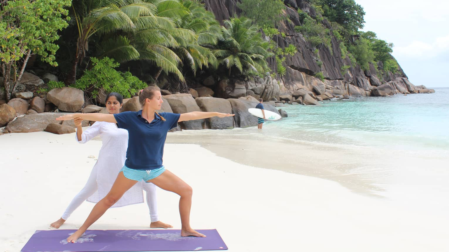 Yogi in white adjusts woman's outstretched arms in yoga pose on white sand beach