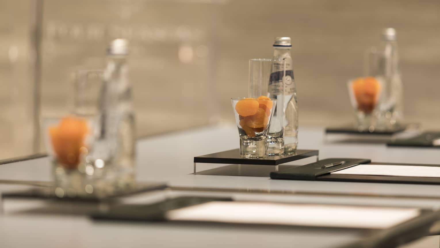 Close-up of meeting table place setting with agenda, dried apricots in glass, bottle of sparkling water