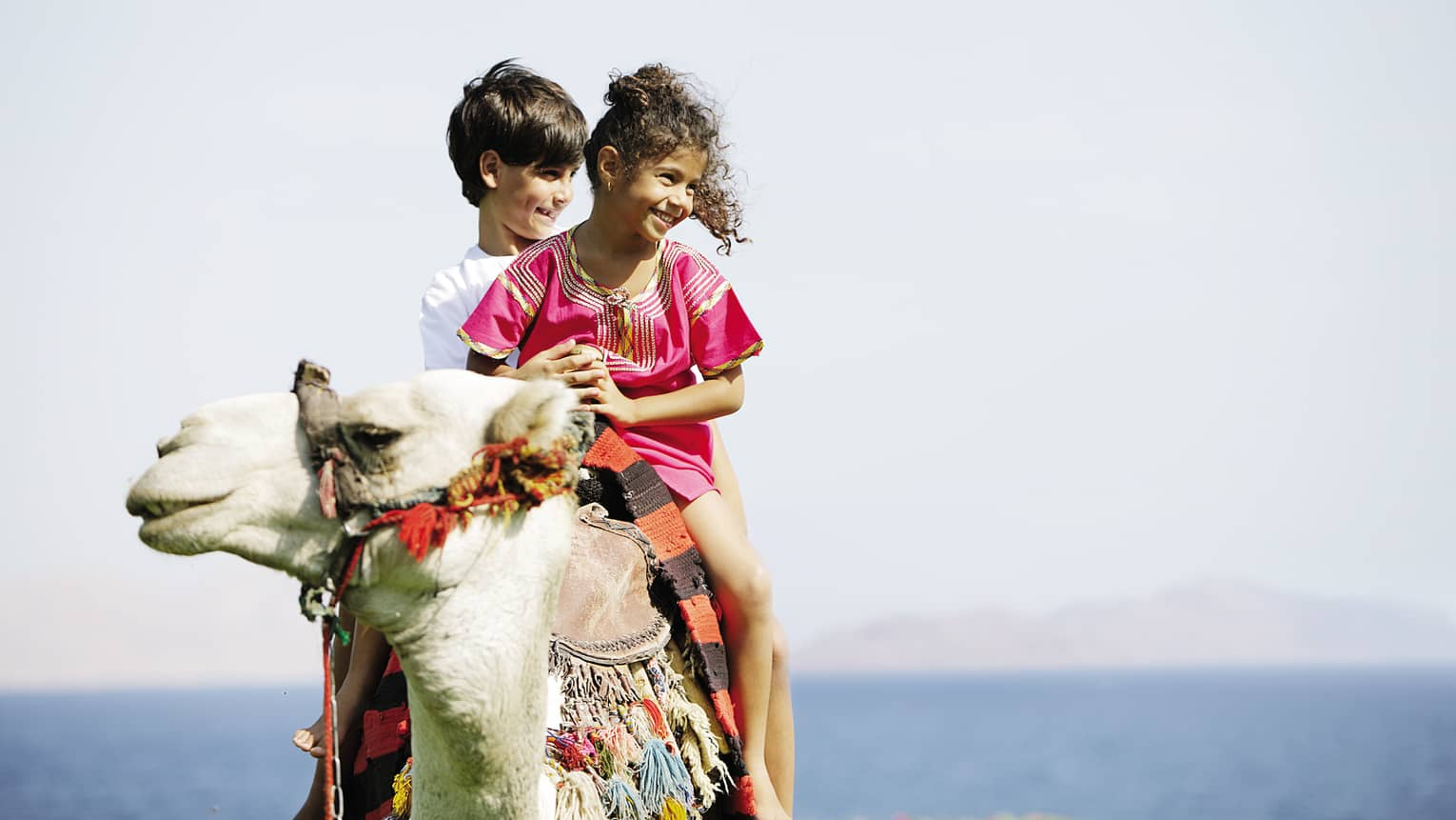 Two smiling children riding on camel