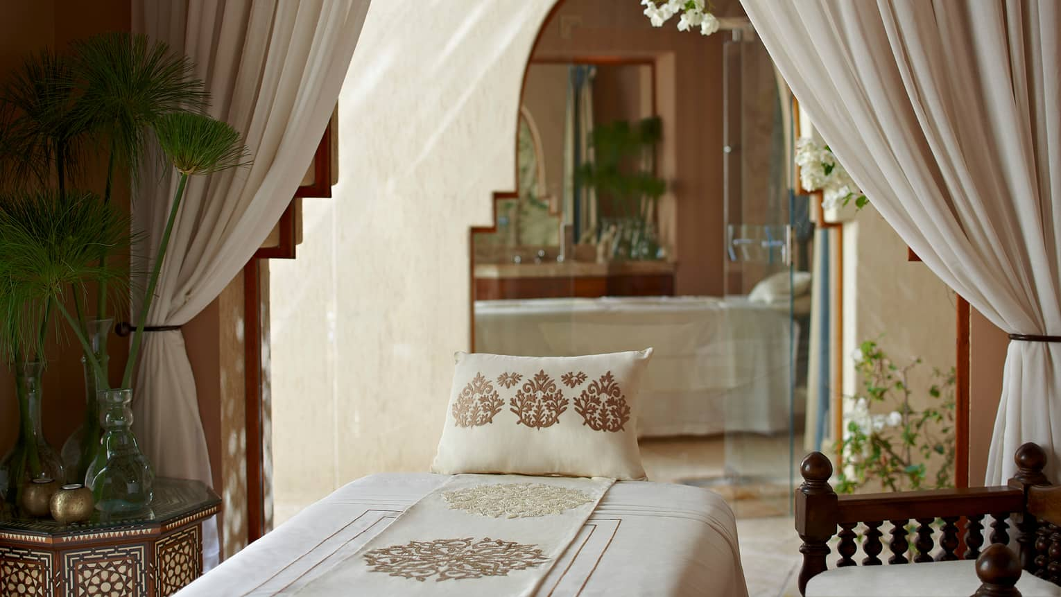 Embroidered pillow, sheet on massage table under white curtains, doorway in Spa