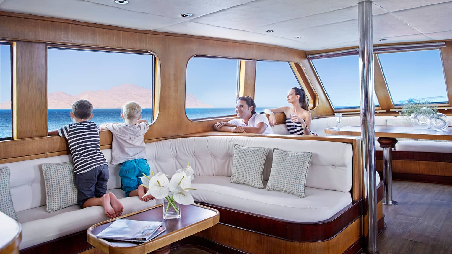 Two children kneel on white L-shaped sofa in yacht, look out window, in front of their smiling parents