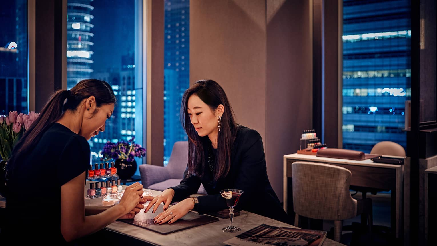 Woman gets manicure at table in hotel salon Nail Bar at night