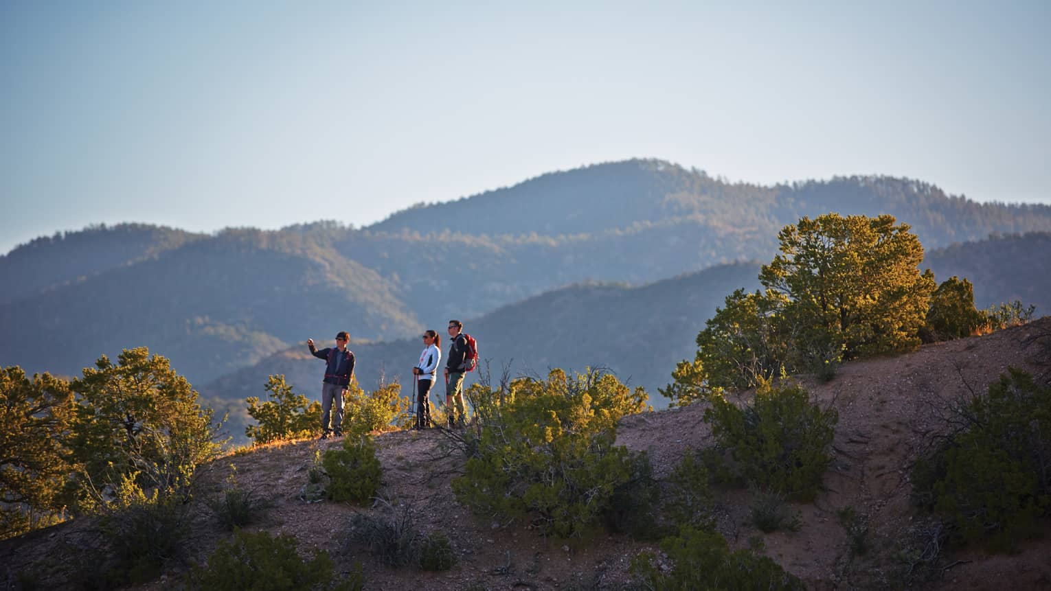Three people hike on desert mountain hill