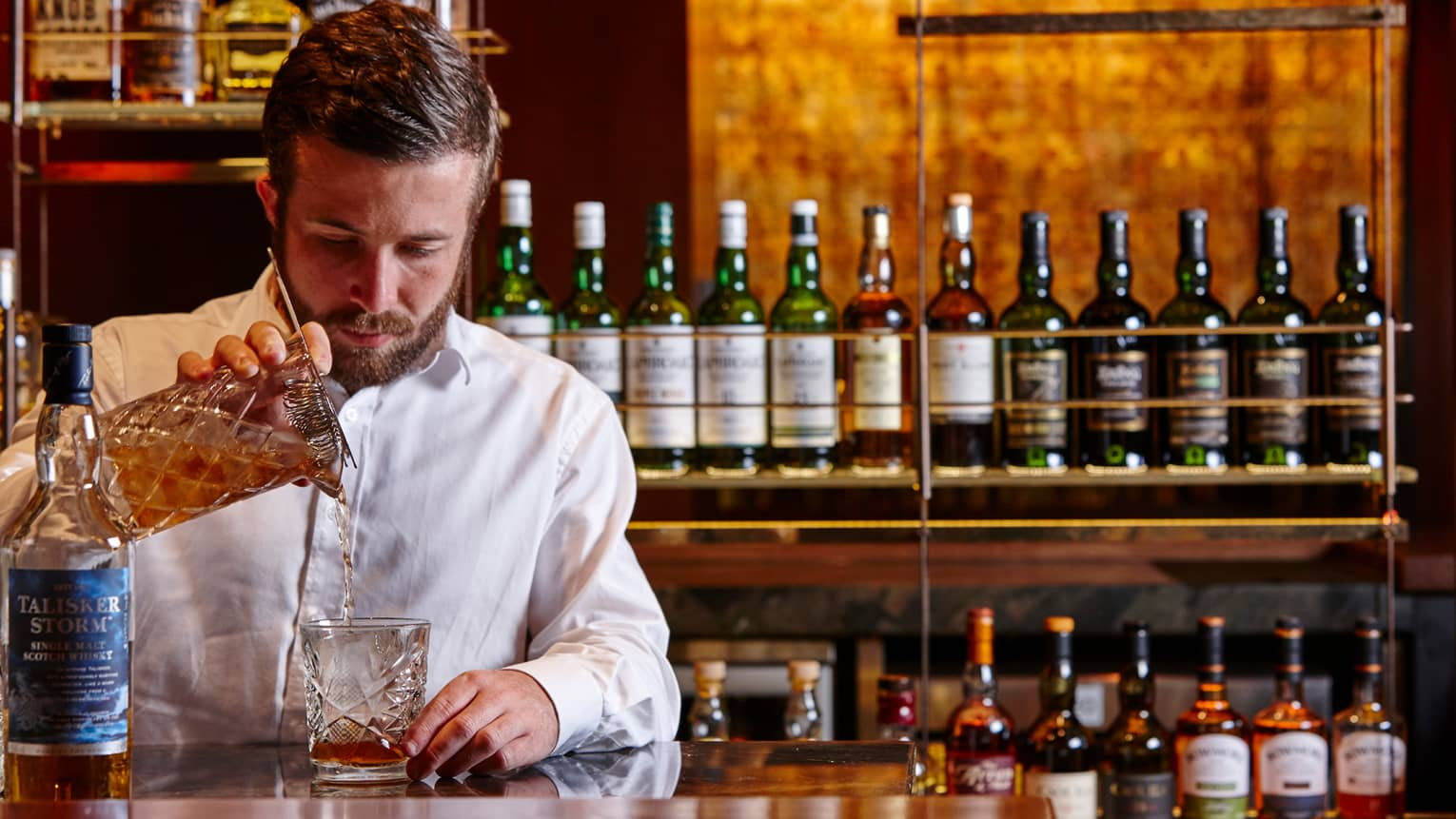 Grain bartender pours single malt whisky from crystal pitcher into glass