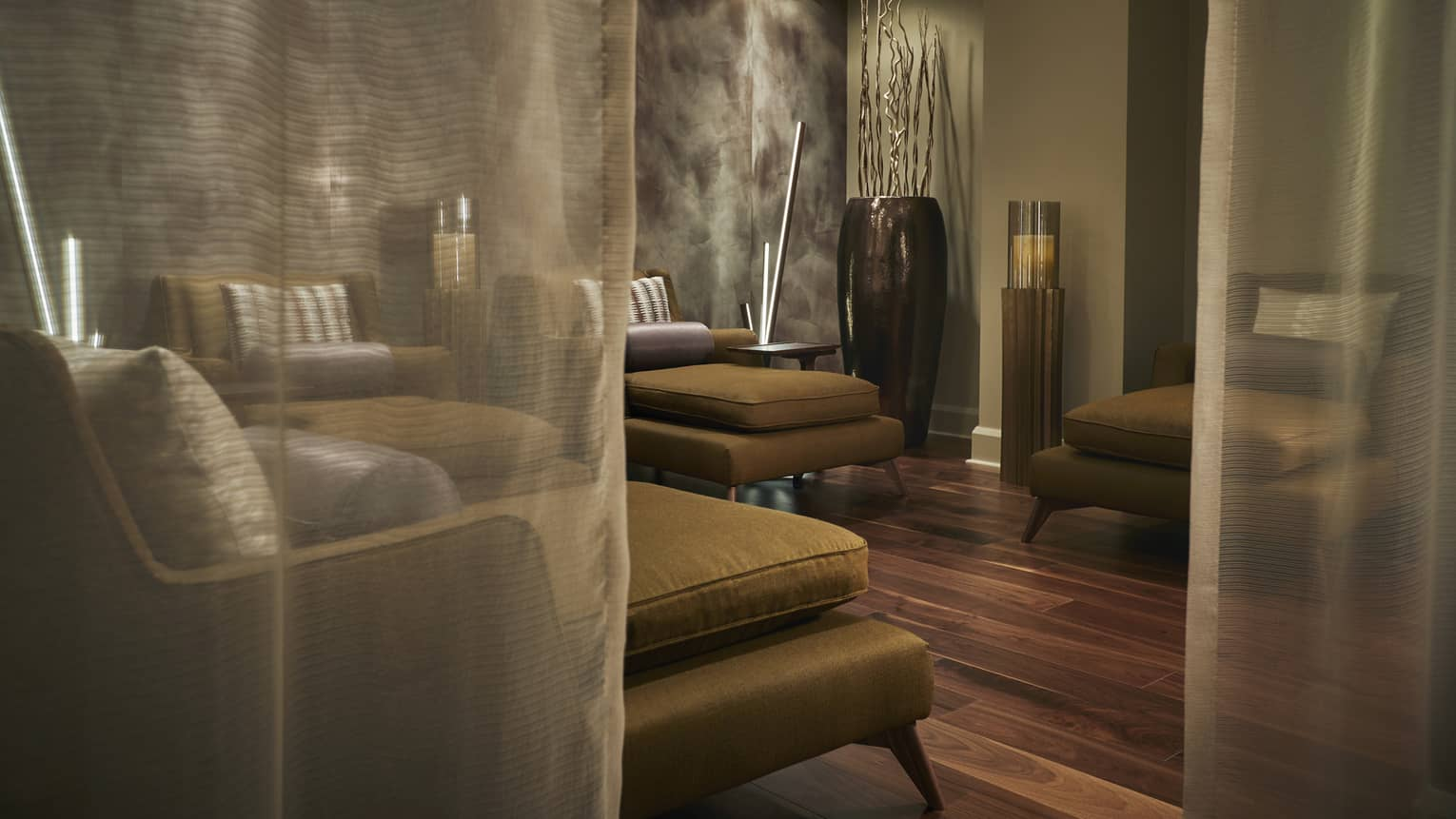 Sheer curtains by plush gold armchairs in Forbes Five Star Spa