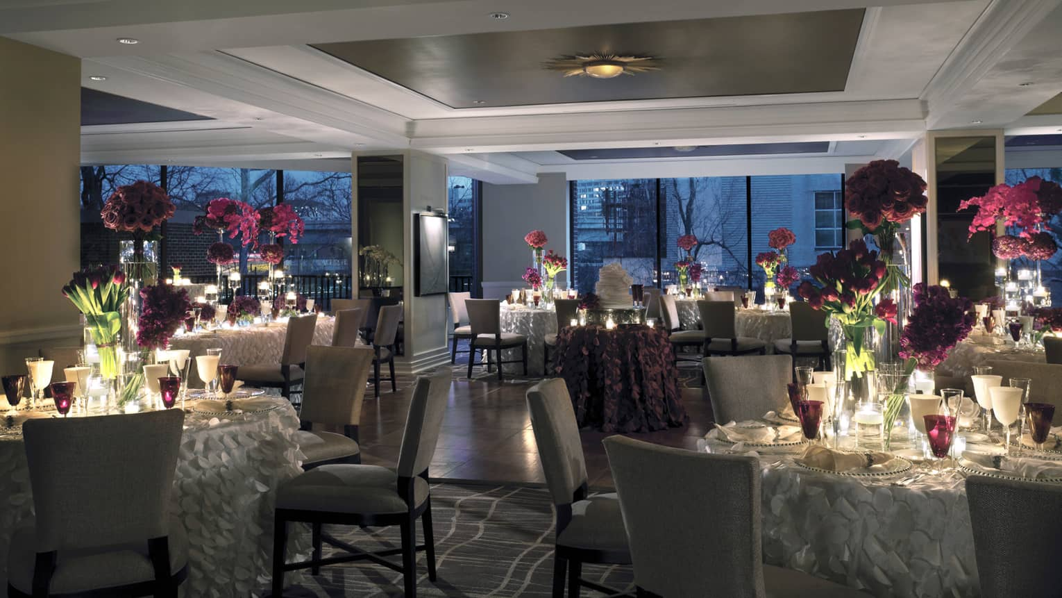 Seasons dining room wedding banquet setting at night with candle-lit tables, fringed tablecloths, floral centrepieces