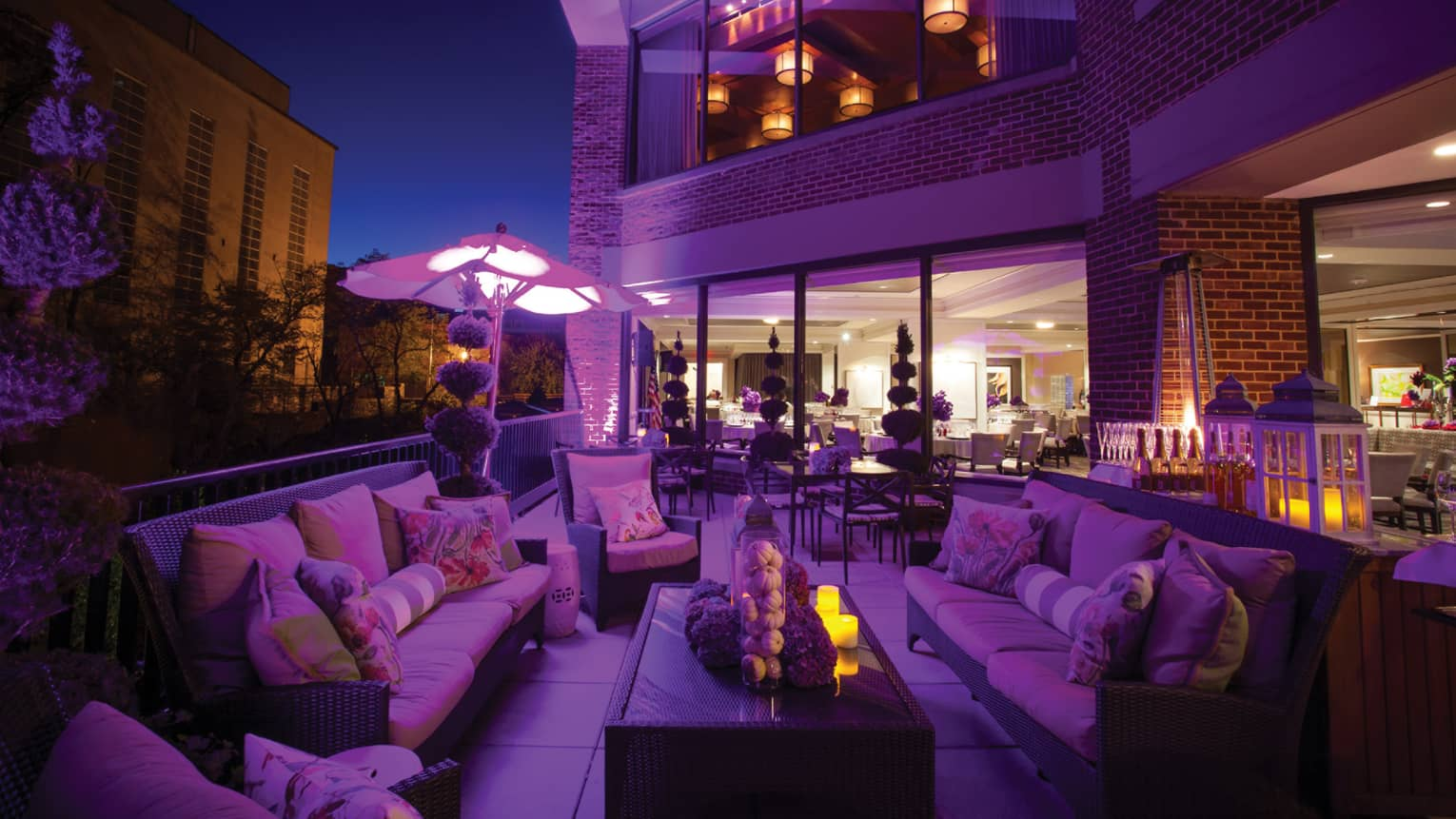 Outdoor Seasons at night with patio banquette lounge chairs, table and sofa, purple hue