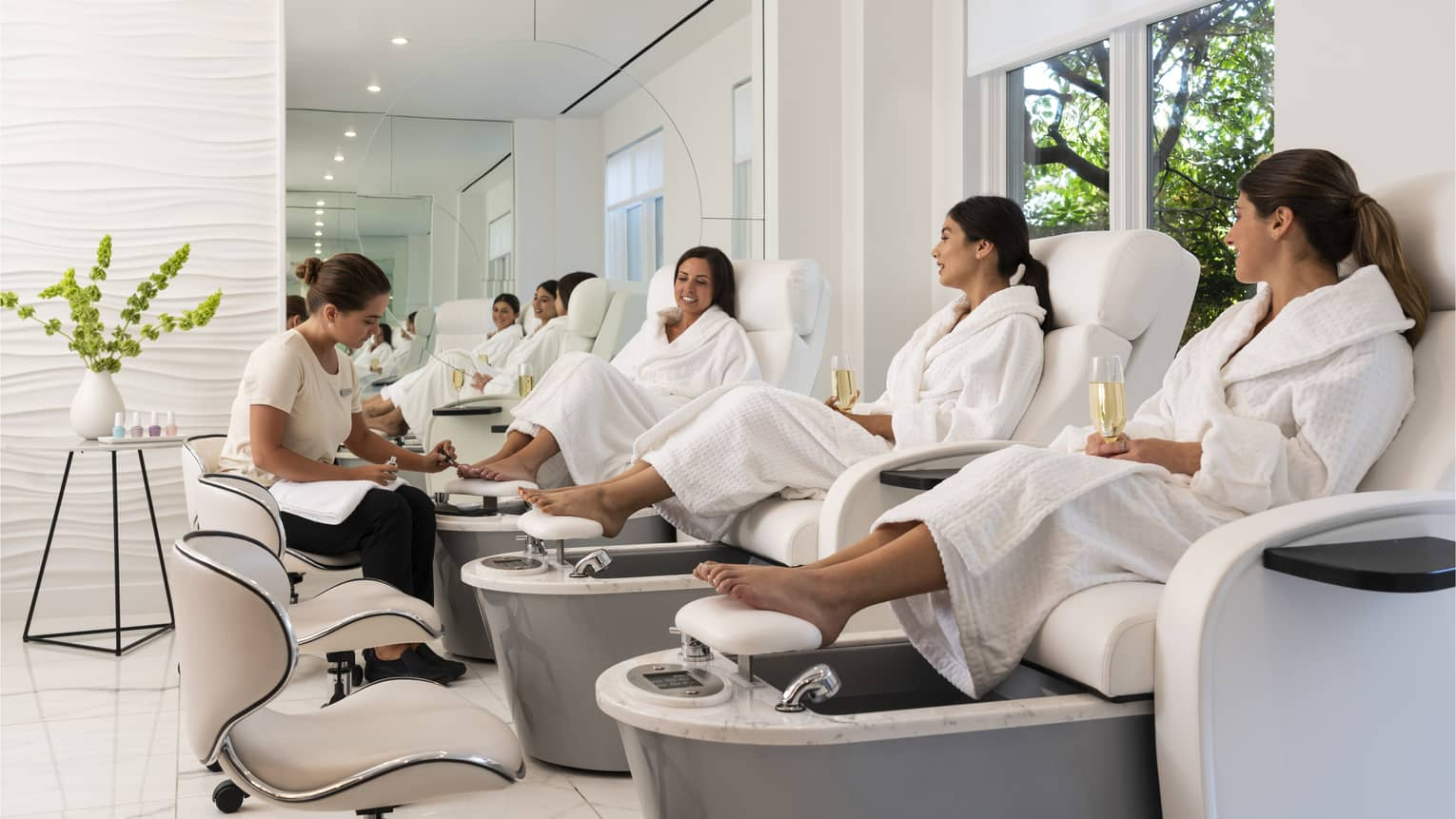 Three women wearing Four Seasons Spa robes sit in pedicure spa chairs, drinking mimosas and chatting white a four seasons technician gives one of them a pedicure