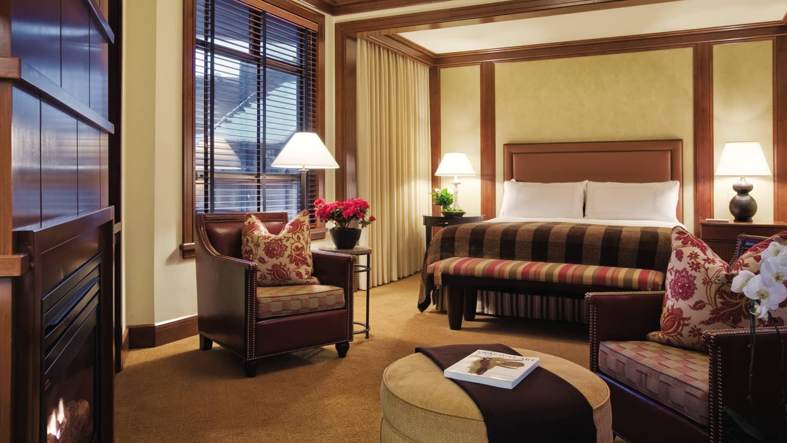 Two-Bedroom Interconnecting Deluxe Suite dimly-lit room with wood accents, bed and chair