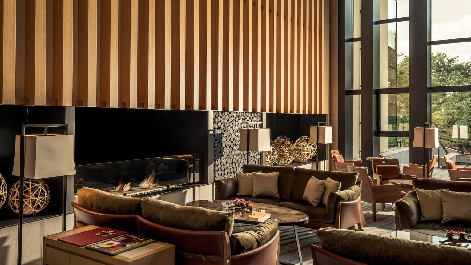 Brasserie brown loveseats, tables by modern fireplace under wood striped wall