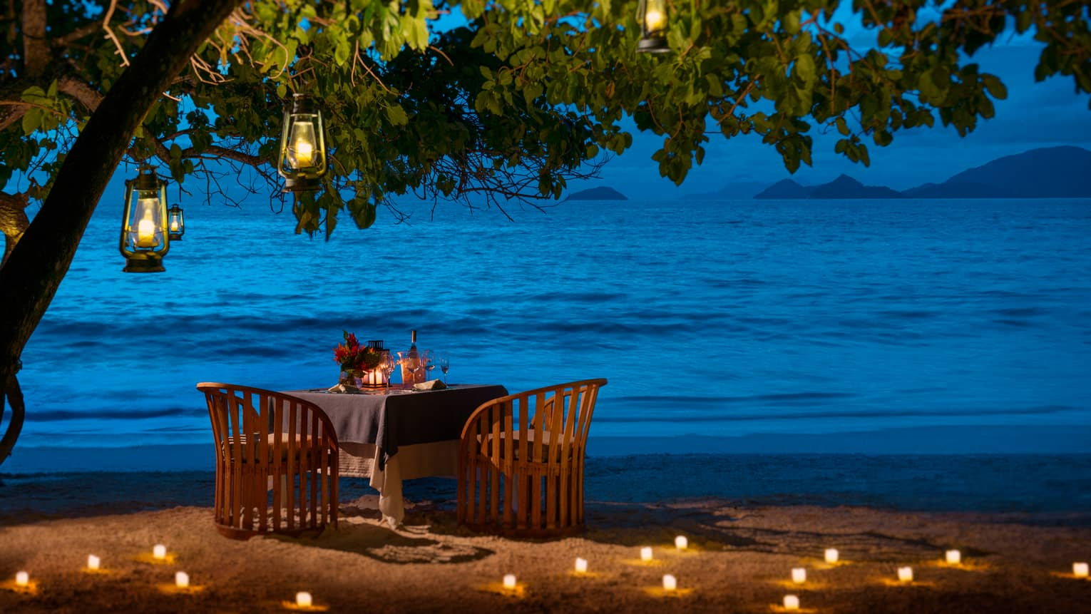 Round candle-lit dining table under tree, lanterns on beach at night