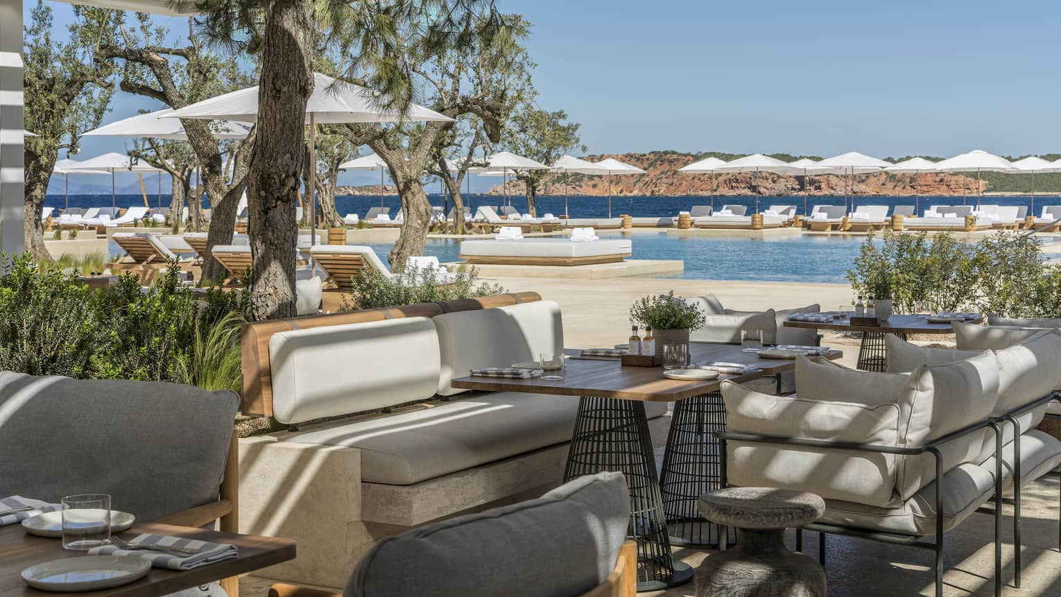 Helios outdoor restaurant with beige benches, modern tables, greenery, surrounding pool and ocean