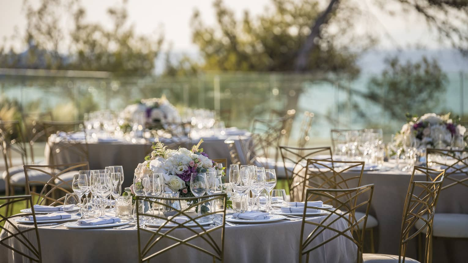 Romantic outdoor table setting with flowers, wine glasses and white linens overlooking trees and ocean