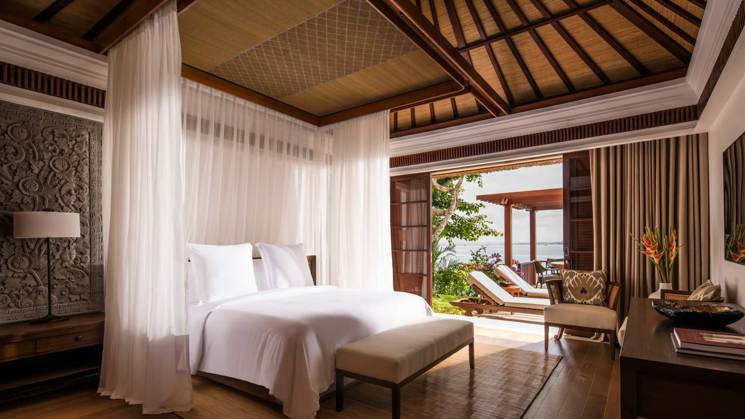 Villa bed with sheer white curtains hanging around each side, Balinese textiles on wall, door open to sunny patio