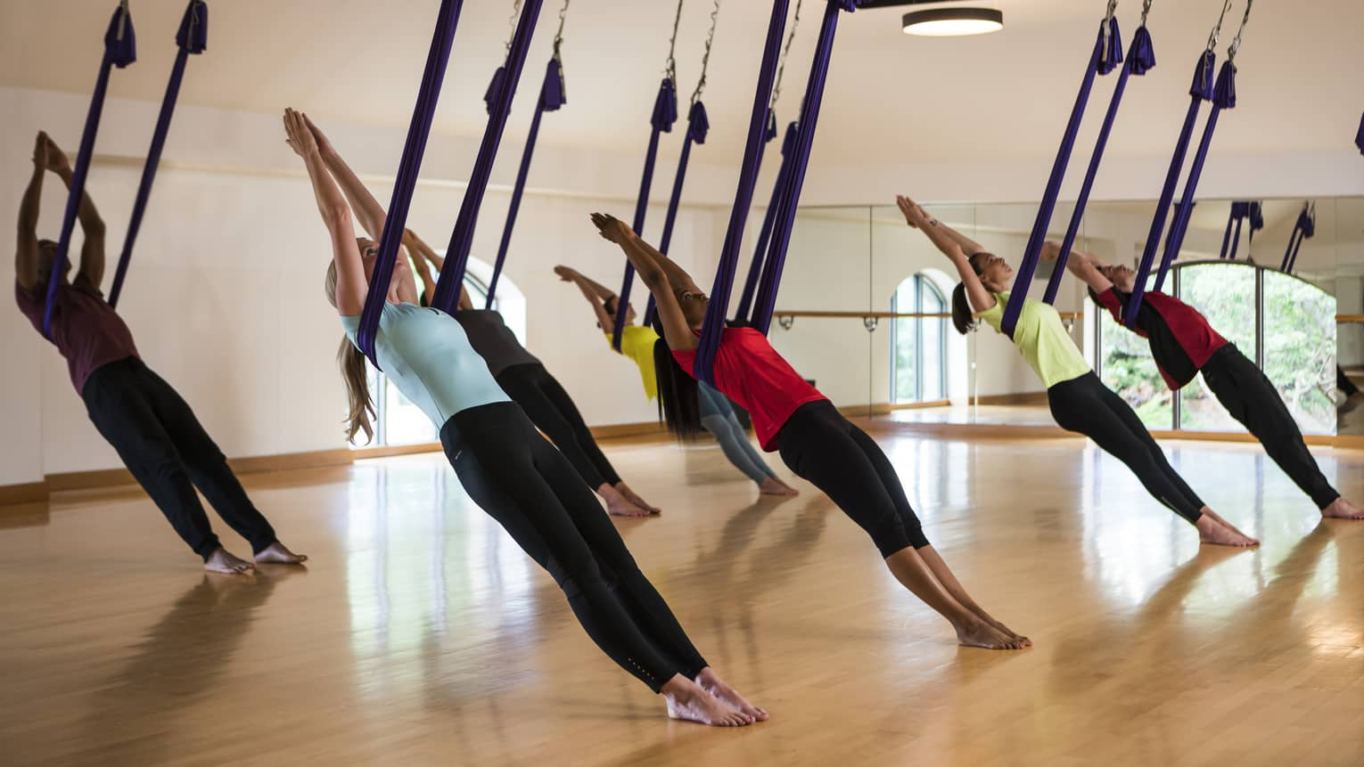 Group of people lean back on small hammocks from ceiling in anti-gravity yoga session