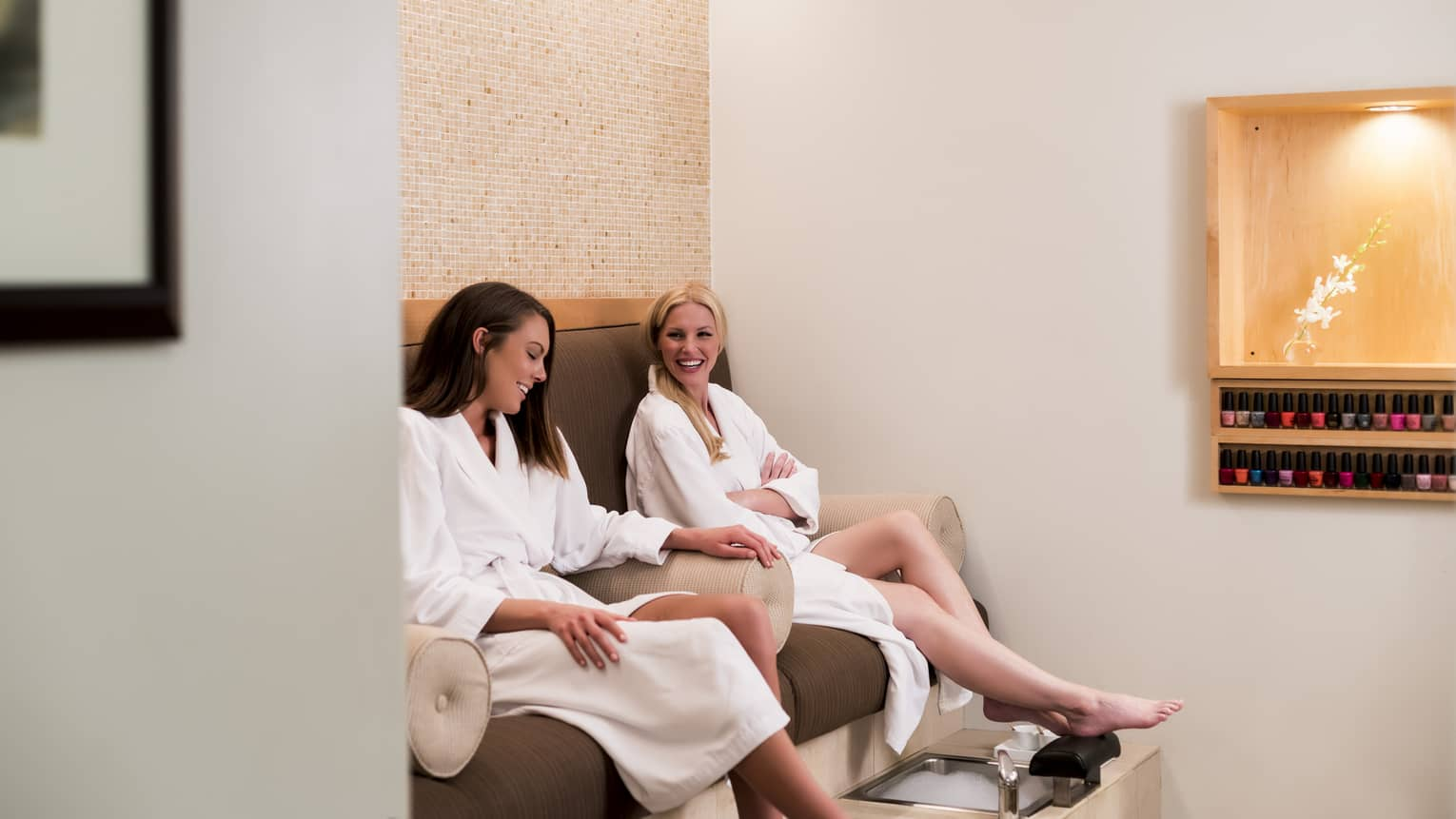 Two women in white bathrobes sit in spa chairs, laugh with feet above pedicure baths