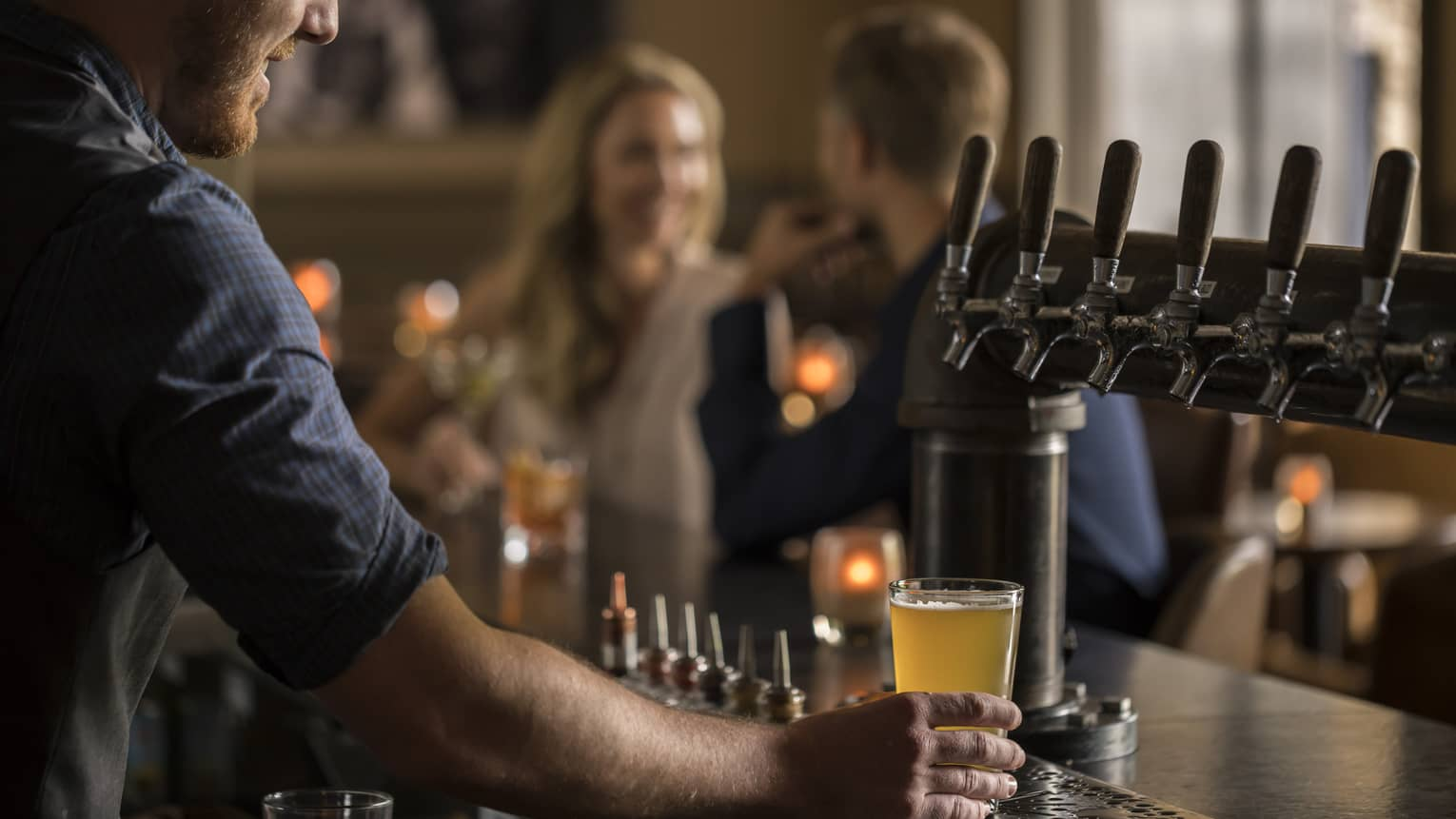 Close-up of bartender pouring beer at taps, couple at bar in background